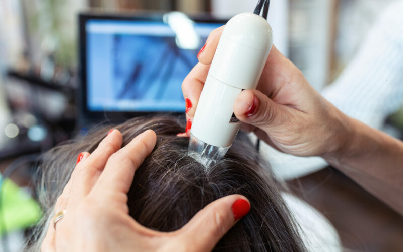 Close-up,Of,Hairdresser,Examining,Client,Hair,With,A,Special,Apparatus